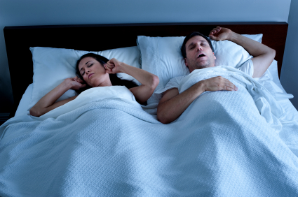 Husband snoring in bed with wife before sleep apnea treatment at LakeView Dental Arts
